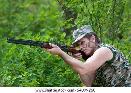Hunter in forest with gun in hand