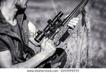 Hunter is aiming. The man is on the hunt. Hunting period. Male with a gun. Close up. Hunter with hunting gun and hunting form to hunt. Hunt hunting rifle. Hunter man. Black and white.