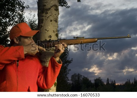 hunter leaning on tree and aiming rifle