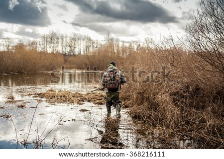 Shutterstock hunter man creeping in swamp during hunting period