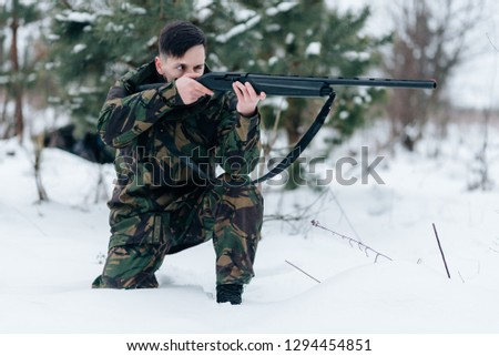 Hunter man dressed in camouflage clothing in the winter pine forest. Armed with a rifle. Concept of hunter man. Hunter with a shotgun