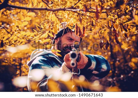 Hunter man hunting. Hunting period, autumn season. Male with a gun. A hunter with a hunting gun and hunting form to hunt in an autumn forest. The man is on the hunt