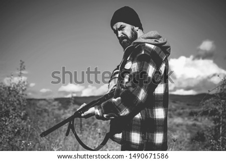 Hunter man hunting. Hunting period. Male with a gun. A hunter with a hunting gun and hunting form to hunt in an autumn forest. The man is on the hunt