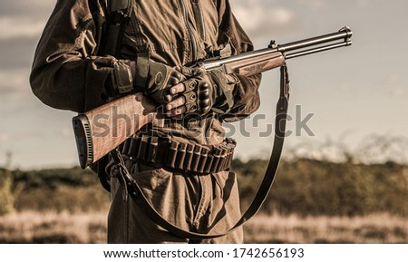 Hunter man. Hunting period, autumn season. Male with a gun. A hunter with a hunting gun and hunting form to hunt in an autumn forest. The man is on the hunt.