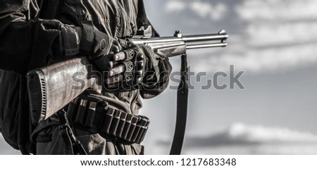 Hunter man. Hunting period, autumn season. The man is on the hunt. Hunter with a backpack and a hunting gun. Male with a gun. A hunter with a hunting gun and hunting form to hunt in an autumn forest.