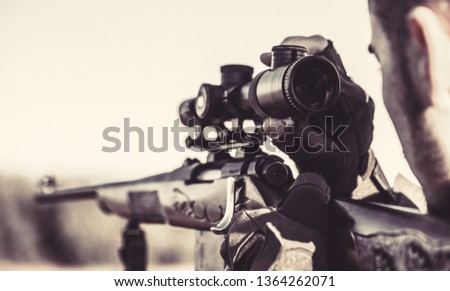 Hunter man. Hunting period. Close up. Hunter with hunting gun and hunting form to hunt. Hunter is aiming. The man is on the hunt. Hunt hunting rifle. Black and white.