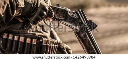 Hunter man. Hunting period. Male with a gun, rifle. Man is charging a hunting rifle. Male hunter in ready to hunt. Closeup. The man is on the hunt, sport.