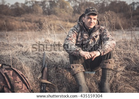 Shutterstock Hunter man in rural field with shotgun and backpack during hunting season