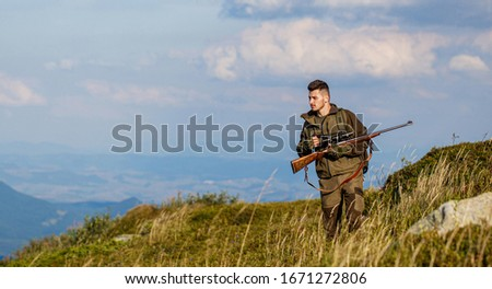 Hunter man. Shooter sighting in the target. Hunting period. Hunter is aiming. The man is on the hunt. Hunt hunting rifle. Hunter with hunting gun and hunting form to hunt sky background.