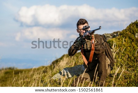 Hunter man. Shooter sighting in the target. Hunting period. Male with a gun. Close up. Hunter with hunting gun and hunting form to hunt. Hunter is aiming. The man is on the hunt. Hunt hunting rifle.