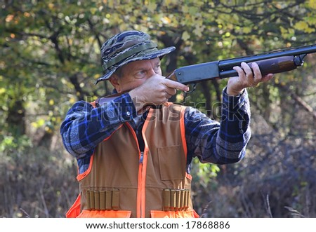 Hunter shooting a shotgun in a field in fall