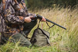 Hunter with a backpack and a hunting gun in the autumn forest. Man is charging a hunting rifle. Close up.