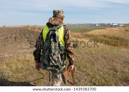 Hunter with a gun and a dog go on the first snow in the steppe, Hunting pheasant in a reflective vest