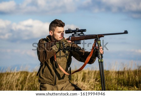 Hunter with hunting gun and hunting form to hunt. Hunter is aiming. Hunter man. Shooter sighting in the target. Hunting period. Male with a gun. Close up. The man is on the hunt. Hunt hunting rifle.