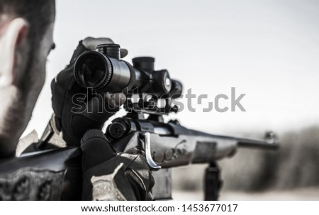 Hunter with hunting gun and hunting form to hunt. Hunter is aiming. Shooter sighting in the target. The man is on the hunt. Hunt hunting rifle. Hunter man. Hunting period. Close up. Black and white.