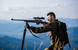 Hunter with hunting gun and hunting form to hunt. Hunter is aiming. The man is on the hunt. Hunt hunting rifle. Hunter man. Shooter sighting in the target. Hunting period. Male with a gun.