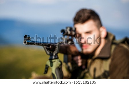 Hunter with hunting gun and hunting form to hunt. Hunter is aiming. The man is on the hunt. Hunt hunting rifle. Hunter man. Shooter sighting in the target. Hunting period. Male with a gun. Close up.