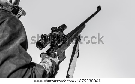 Hunter with hunting gun and hunting form to hunt. Hunter is aiming. The man is on the hunt. Hunt hunting rifle. Hunter man. Black and white.