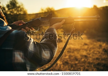 Hunter with shotgun gun on hunt. Illegal Hunting Poacher in the Forest. American hunting rifles. Hunting without borders