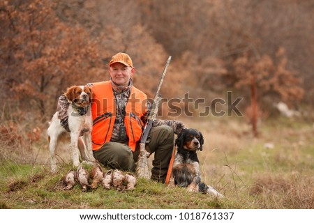 Shutterstock hunter with two hunting dogs, a gun and a woodcock after a hunt