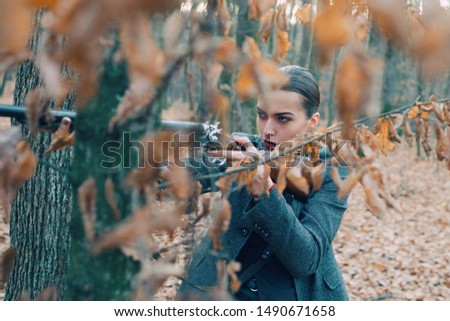 Hunter woman. Hunting period, autumn season. Female with a gun. A hunter with a hunting gun and hunting form to hunt in an autumn forest. Woman is on the hunt. Hunter with a backpack and a hunting gun