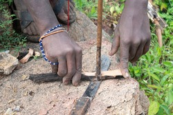 Hunters from Hadzabe tribe in Tanzania. Making a fire with wood stick friction.