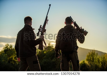 Hunters rifles nature environment. That was great day. Finish hunting season. Enjoy sunset in mountains. Hunters friends enjoy leisure. Hunters friends gamekeepers with guns silhouette sky background.