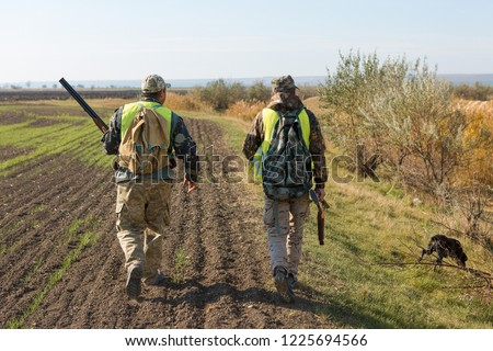 Hunters with a german drathaar and spaniel, pigeon hunting with dogs in reflective vests