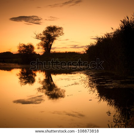 hunting and fishing in the pond. Evening landscape of the river and sky and trees reflected in water.