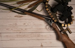 Hunting equipment. Hunting weapon, bandoleer with cartridges, binoculars on a light wooden background.