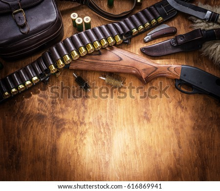 Shutterstock Hunting equipment - pump action shotgun, 12 mm hunting cartridge  and hunting knife on the wooden table.