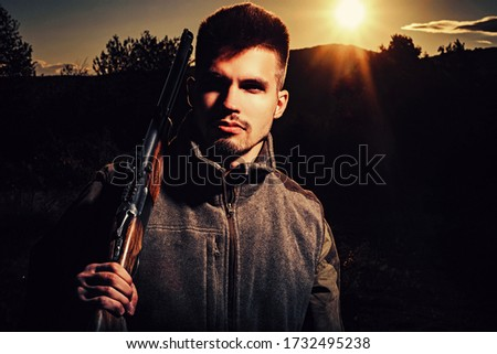 Hunting Gear - Hunting Supplies and Equipment. Hunter with shotgun gun on hunt. Illegal Hunting Poacher in the Forest. Close up Portrait of hamdsome Hunter