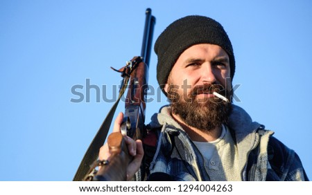 Hunting masculine hobby concept. Man brutal bearded guy gamekeeper blue sky background. Brutality and masculinity. Hunter with rifle gun close up. Guy bearded hunter spend leisure hunting and smoking.