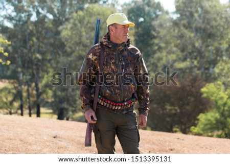 Hunting period, autumn season open. A hunter with a gun in his hands in hunting clothes in the autumn forest in search of a trophy.