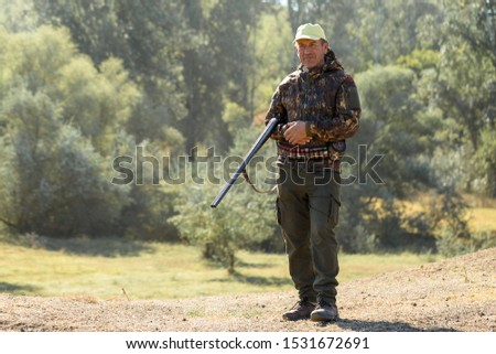 Hunting period, autumn season open. A hunter with a gun in his hands in hunting clothes in the autumn forest in search of a trophy. A man stands with weapons and hunting dogs tracking down the game.