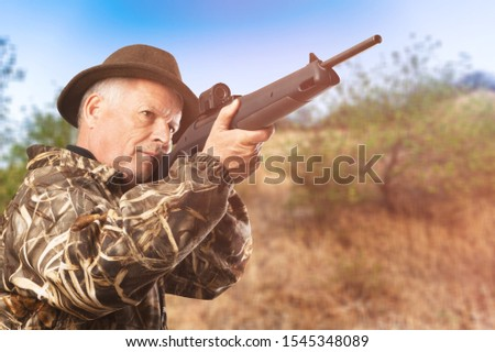 Hunting period. Male with a gun. Close up. Hunter with hunting gun and hunting form to hunt. Hunter is aiming. Shooter sighting in the target. The man is on the hunt. Hunt hunting rifle. Hunter man.