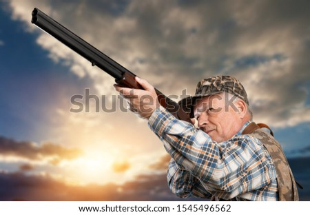 Hunting period. Male with a gun. Hunter with hunting gun and hunting form to hunt. Hunter is aiming. Shooter sighting in the target. The man is on the hunt. Hunt hunting rifle