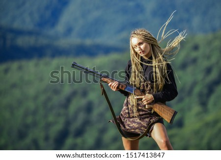 Hunting season. Woman attractive long hair pretty face hold rifle for hunting. Dangerous girl. Defending concept. Sexy warrior. She is warrior. Warrior mountains landscape background. Feminist girl.