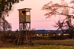 Hunting tower after sunset in rural scenery against pink sky. Deer stand near Zettling Graz in Austria. Hunting concept
