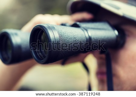 hunting, war, army and people concept - close up of young soldier, ranger or hunter with binocular observing forest Stockfoto ©