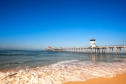 Huntington Beach Pier during early morning shows the tides changing with rushing surf moving up the shoreline.