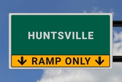 Huntsville logo. Huntsville lettering on a road sign. Signpost at entrance to Huntsville, USA. Green pointer in American style. Road sign in the United States of America. Sky in background