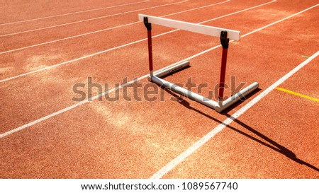hurdle race barrier obstacle on red  running track , athletic stadium