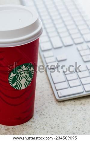Hurricane Utah - November 29 : photo of a holiday Starbucks cup next to a computer keyboard, November 29 2014 in Hurricane, Utah