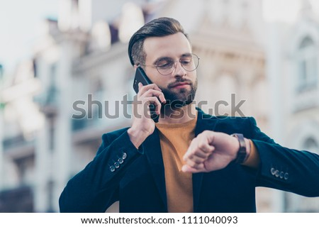Hurry up! Portrait of responsible attractive man with modern hairdo having important call speaking by smart phone looking at luxury watch on wrist isolated on blurred background. Accessory concept