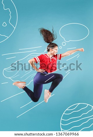 Hurry up to save the universe. Dreaming about cosmonaut profession or travel the cosmos. Young woman in drawing imaginary spacesuit against blue background. Concept of childhood and dreams. #1367069966