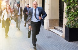 Hurrying business people with stressed man in foreground running on city street.