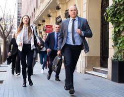 Hurrying business people with stressed man in foreground running on city street..