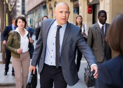 Hurrying businessman in formal suit with briefcase in hand running on city street in crowd of people..