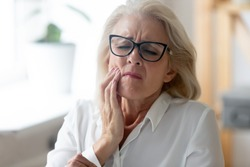 Hurt senior female worker in glasses feel stressed suffering from severe toothache at workplace, unhappy aged woman employee in glasses feel bad stressed having teeth pain, need dental treatment